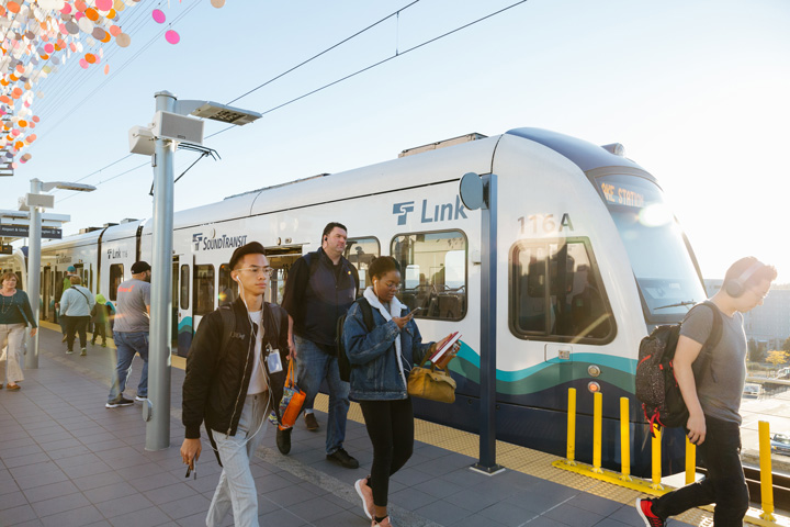 People embarking and disembarking a link light rail train
